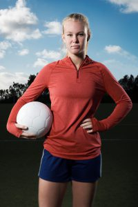 This is a portrait of a 15 year old teenage girl holding a soccer ball out on a field. She is looking seriously into the camera with a tough competitive spirit.