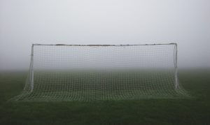 A goal and football pitch stand empty in very foggy weather.